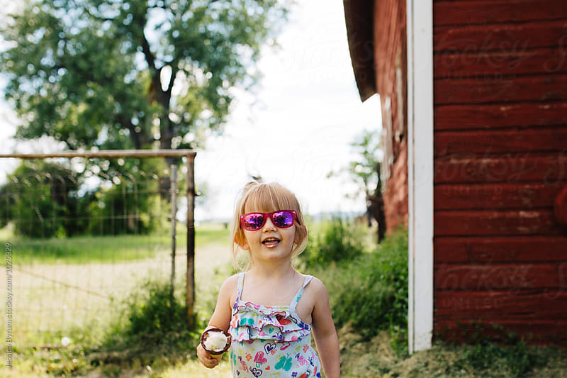 Toddler girl eating an ice cream cone and laughing by Jessica Byrum for Stocksy United