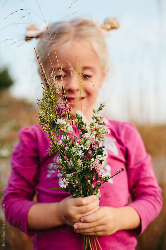 cute girl holding wildflowers by Brian Powell for Stocksy United