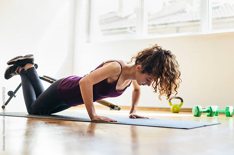 Young woman making push ups at home by Aleksandar Novoselski for Stocksy United