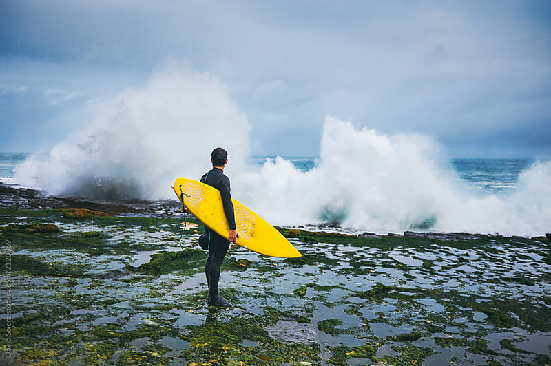 Surfer looking at the waves crushing on the cliff by David Sciora for Stocksy United
