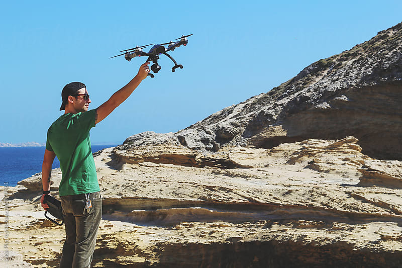 Photographer using a drone over a cliff by Luca Pierro for Stocksy United