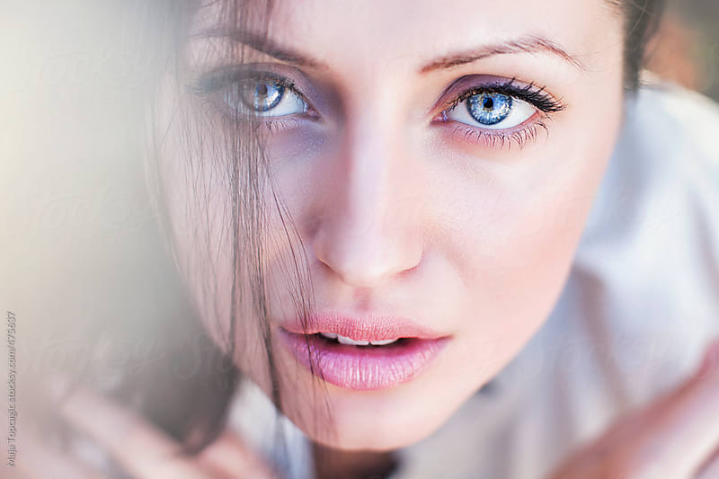 Portrait of a beautiful young woman with black hair and blue eyes by Maja Topcagic for Stocksy United
