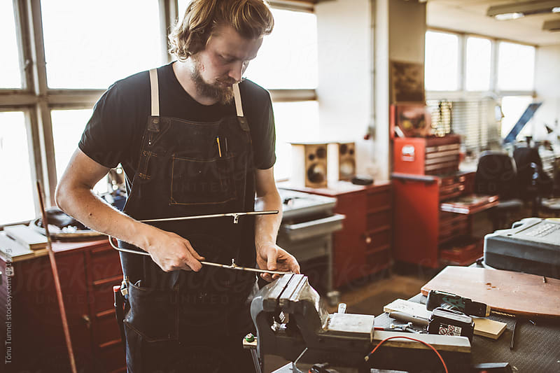 A craftsman building custom parts for a bicycle by Tõnu Tunnel for Stocksy United