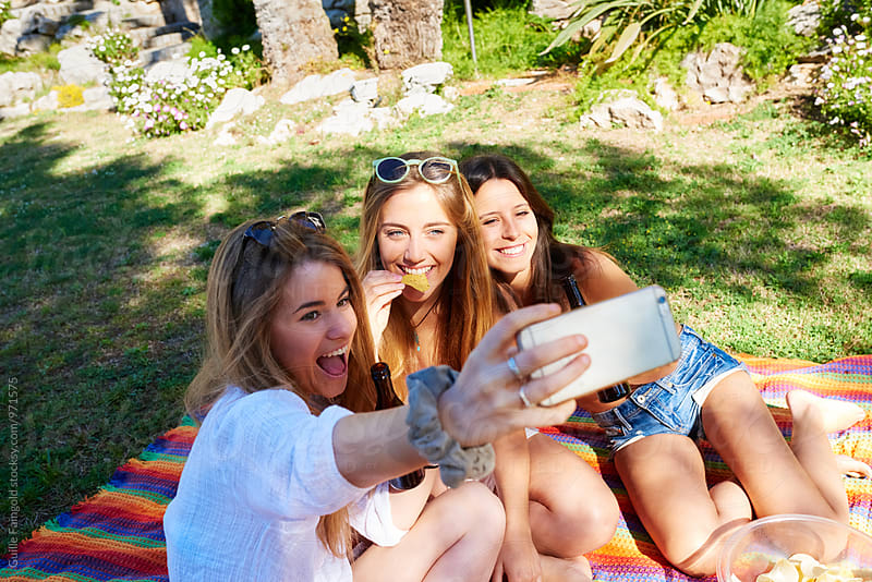 Happy girlfriends taking selfie on backyard  by Guille Faingold for Stocksy United