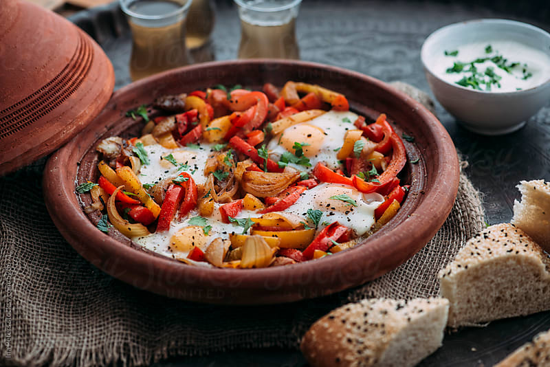 Food: Shakshuka with Bell Pepper, Onions and eggs in Tagine by Ina Peters for Stocksy United