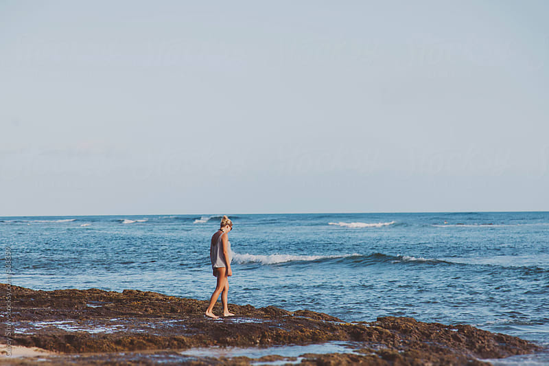Young woman walking along beach by Carey Shaw for Stocksy United