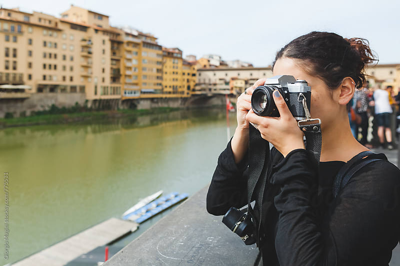 Young Woman Taking Pictures by an Italian River with an Analog Camera by Giorgio Magini for Stocksy United