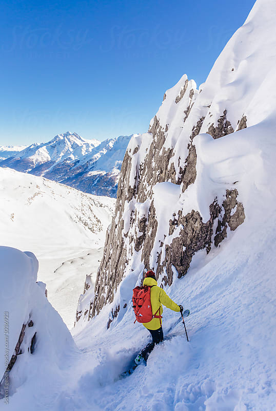 Skier skiing a steep rocky mountain couloir by Soren Egeberg for Stocksy United