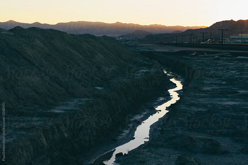 Industrial runoff and small stream, desert landscape in distance, dusk by Paul Edmondson for Stocksy United