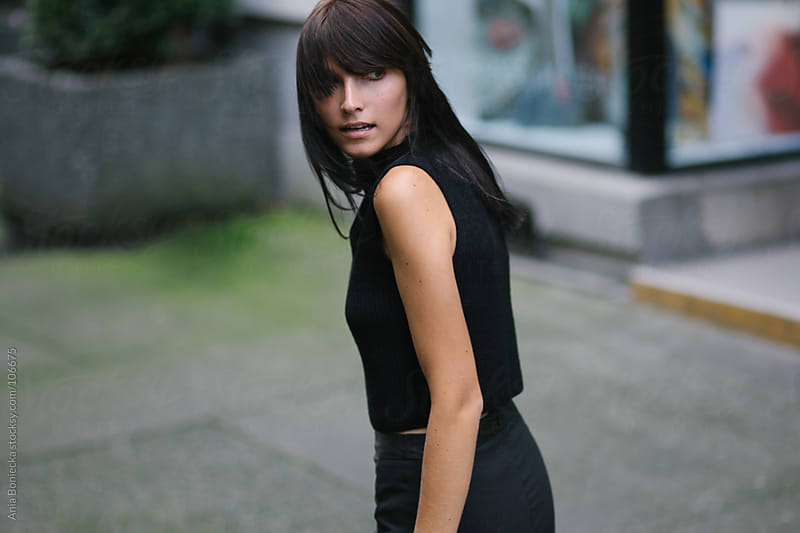 A brunette walking and looking back by Ania Boniecka for Stocksy United
