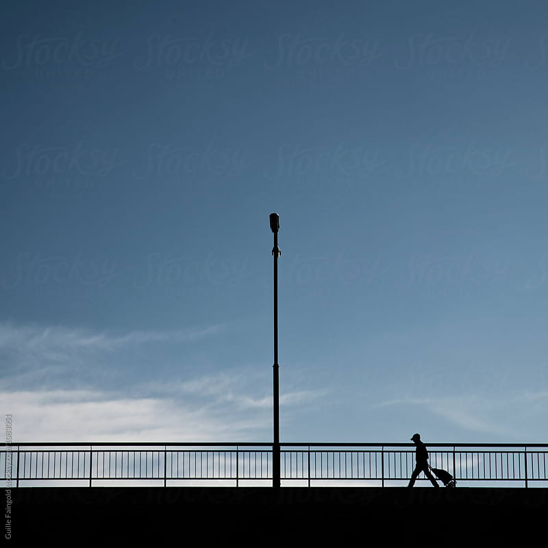 Silhouette of traveler walking along bridge by Guille Faingold for Stocksy United