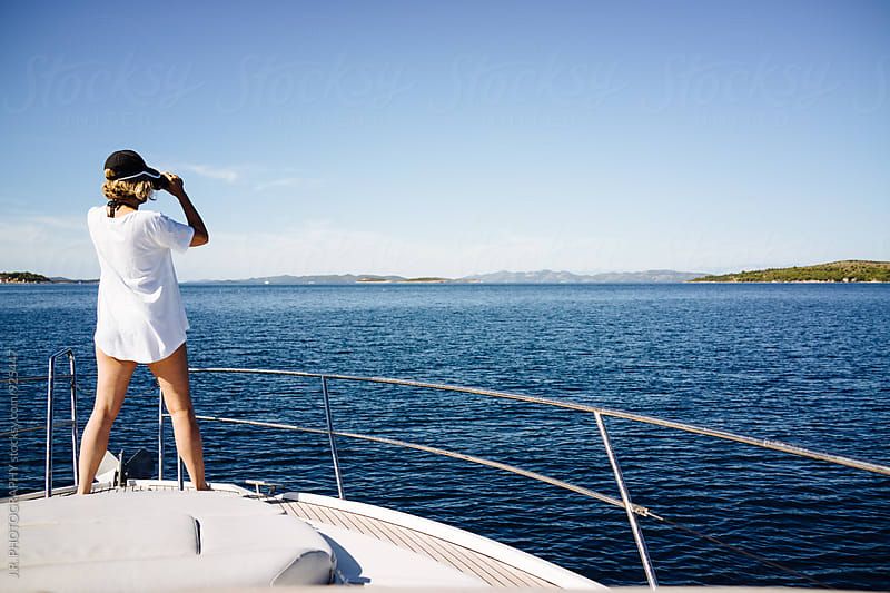 Woman on yacht using binoculars by J.R. PHOTOGRAPHY for Stocksy United