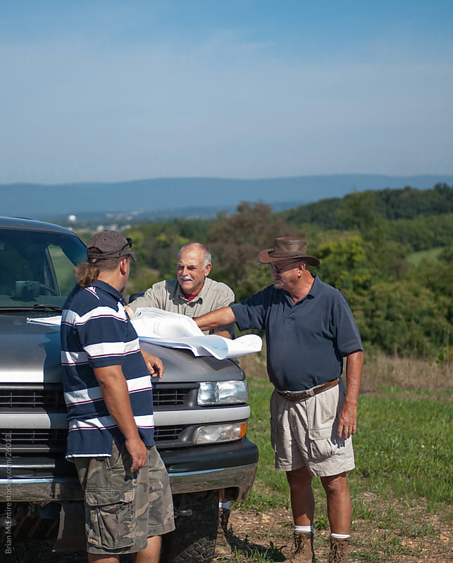 Land Survey Crew Examines Blue Prints on Truck by Brian McEntire for Stocksy United