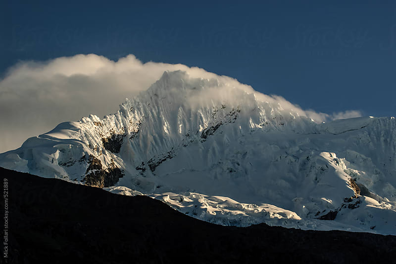 High altitude mountain with clouds in dramatic light by Mick Follari for Stocksy United
