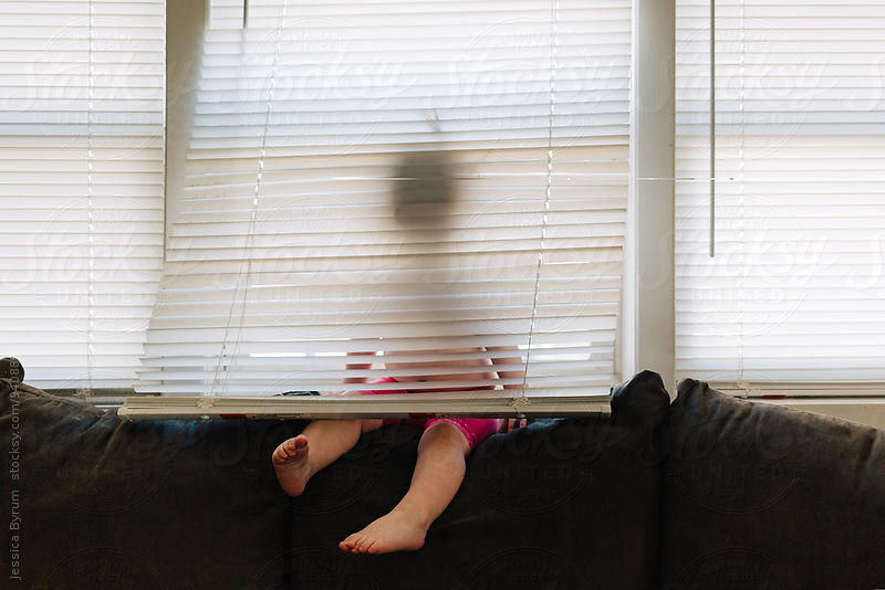 Little girl sitting behind blinds by Jessica Byrum for Stocksy United