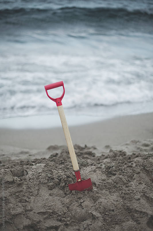 Red shovel digged on the sand of the beach by Lydia Cazorla for Stocksy United