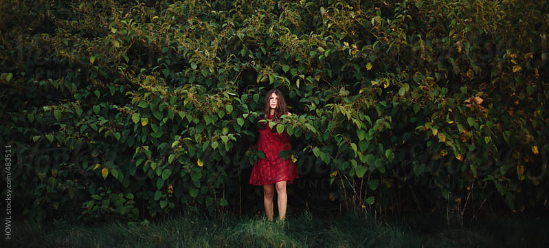 Female in red dress emerges from the bushes. by HOWL for Stocksy United