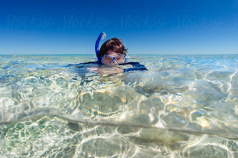 Boy with snorkel set half submerged in shallow clear ocean water by Angela Lumsden for Stocksy United