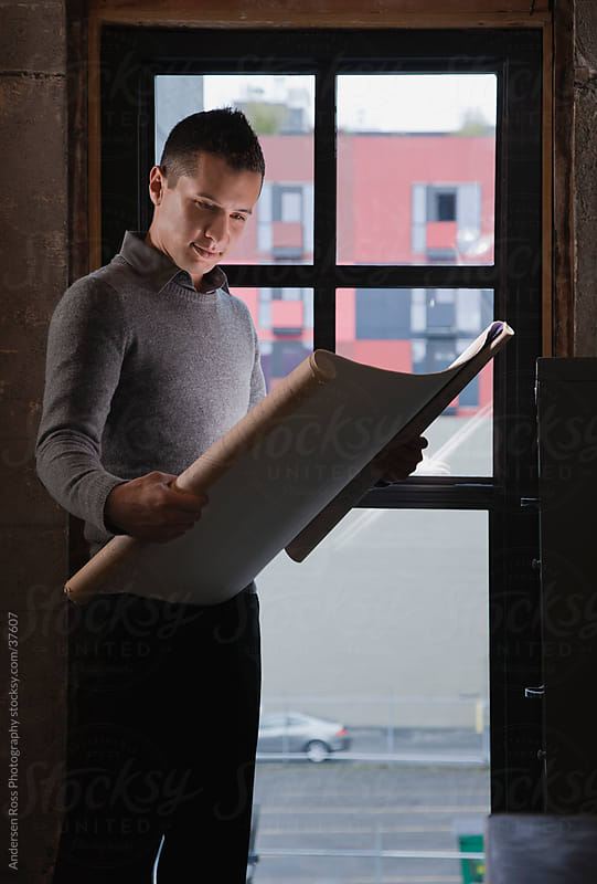 Man looking at blueprints by Andersen Ross Photography for Stocksy United