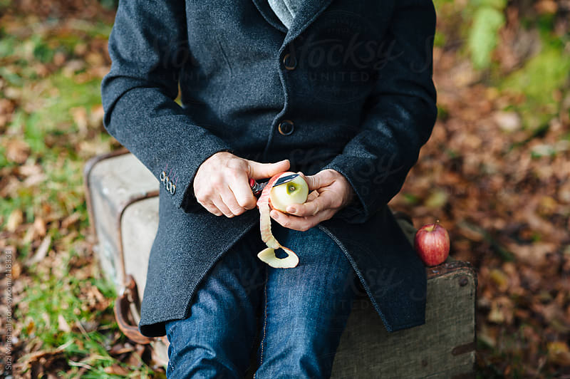Man peeling an apple outdoors by Suzi Marshall for Stocksy United