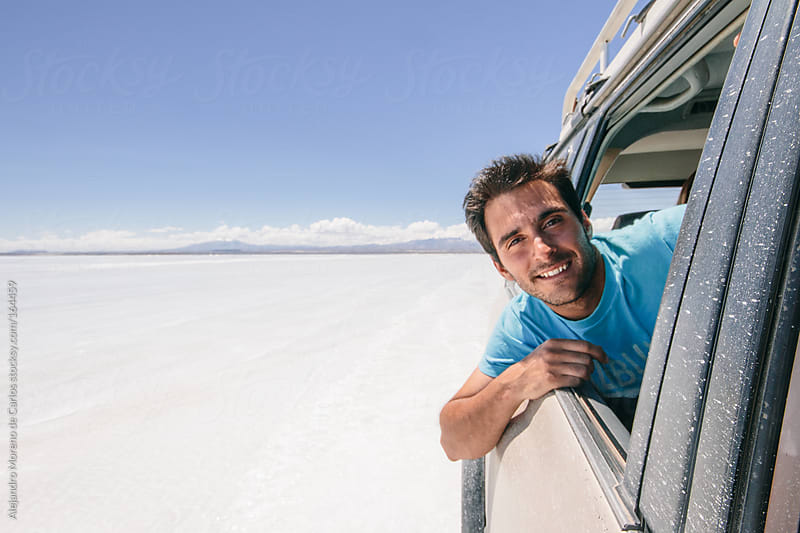 Young man on all terrain car on adventure travel in Uyuni, Bolivia by Alejandro Moreno de Carlos for Stocksy United