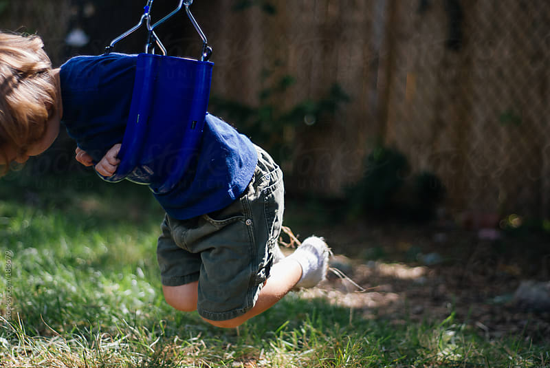 Little boy swings on a play set on his belly by Cara Dolan for Stocksy United