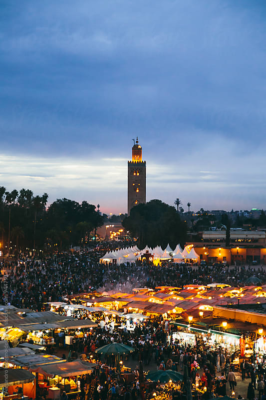 Illuminated mosque tower over outdoor market at sunset. Marrakech, Morocco by Alejandro Moreno de Carlos for Stocksy United