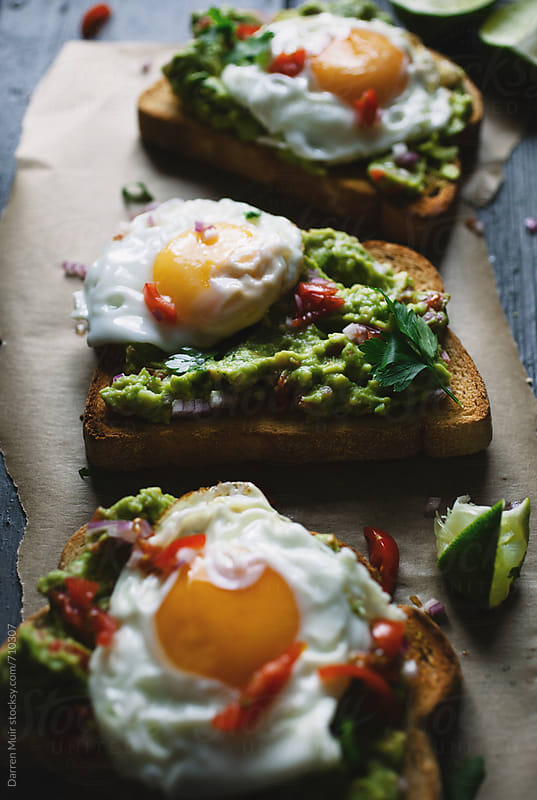Avocado and fried egg toasted open sandwiches.  by Darren Muir for Stocksy United