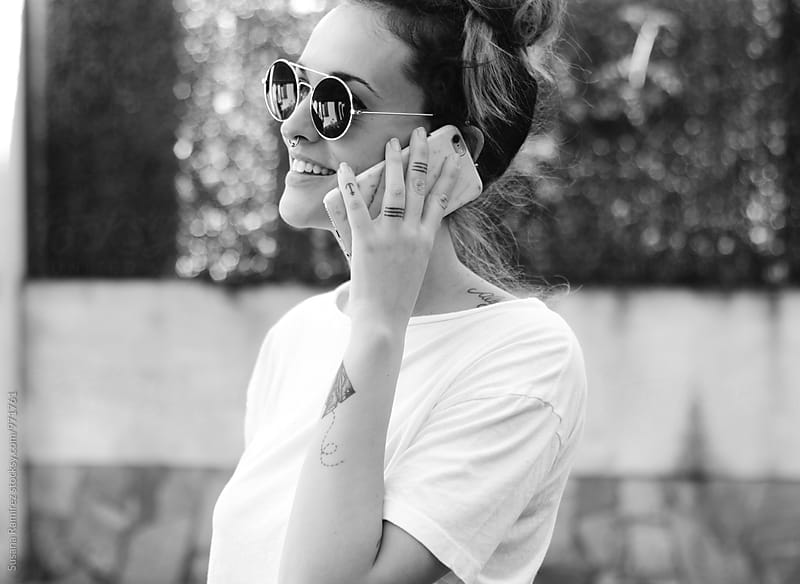 Portrait of young woman talking on mobile phone by Susana Ramírez for Stocksy United