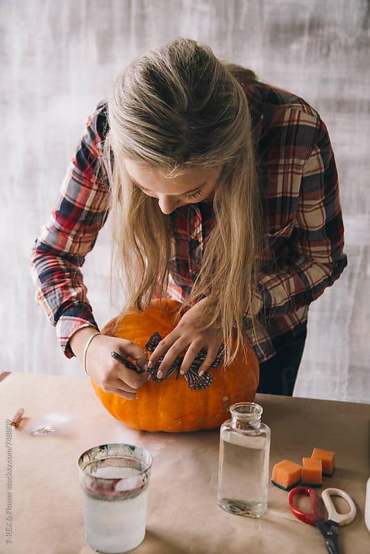 Girl making pattern on pumpkin by Danil Nevsky for Stocksy United