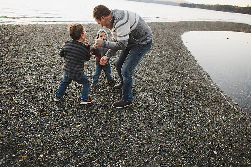 Young dad playingrough with sons at beach by Rob and Julia Campbell for Stocksy United