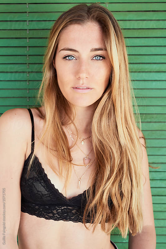 Attractive blonde girl with blue eyes and black lace bra by Guille Faingold for Stocksy United