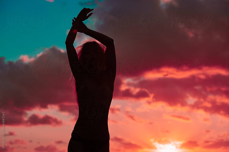 Female Silhouette against a Vivid Sunrise by WAA for Stocksy United