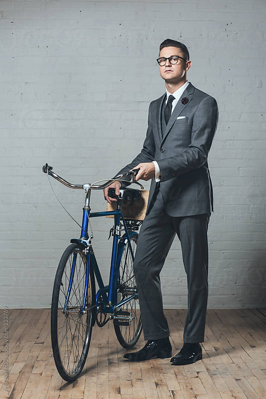 A handsome young man standing beside his bicycle wearing a suit by Ania Boniecka for Stocksy United