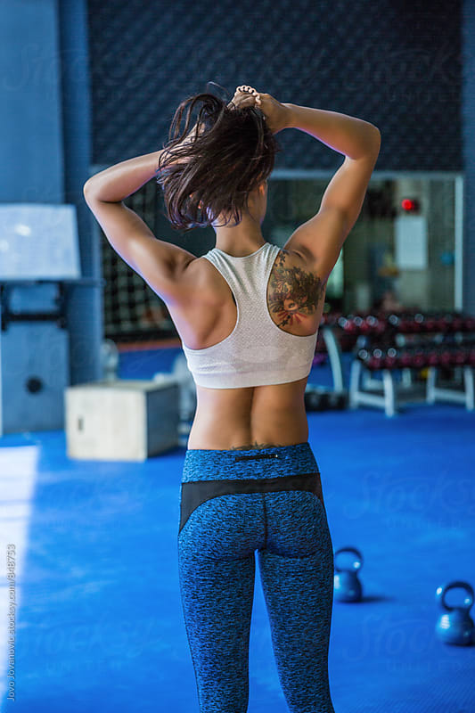 Fit tattooed woman fixes her hair mid-workout by Jovo Jovanovic for Stocksy United