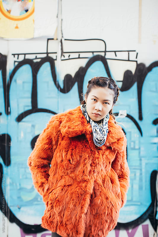 Outdoor Portrait of Fashionable Young Japanese Woman Standing in Front of Blue Graffiti by VISUALSPECTRUM for Stocksy United