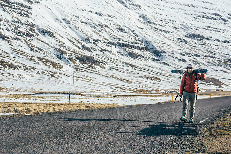 Skier walking alone carrying skis long an empty road in Iceland by Søren Egeberg Photography for Stocksy United
