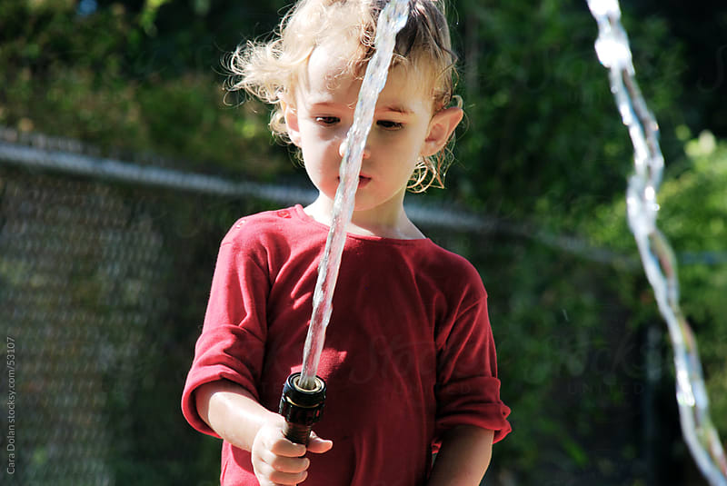 Young boy plays with water hose outside by Cara Slifka for Stocksy United
