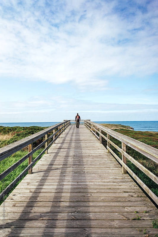 Man walking on a wooden walkway by ACALU Studio for Stocksy United