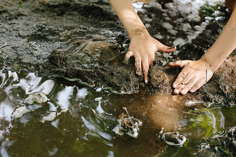 girl's hands playing the mud by Brian Powell for Stocksy United