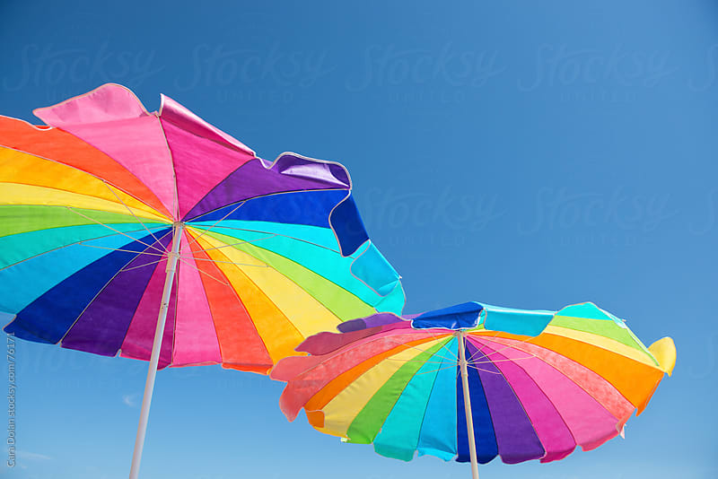 Colorful beach umbrellas against a blue summer sky  by Cara Slifka for Stocksy United