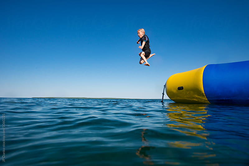 Boy Jumping Into Summer Lake From Water Trampoline At Cottage on Bright Sunny Day by JP Danko for Stocksy United