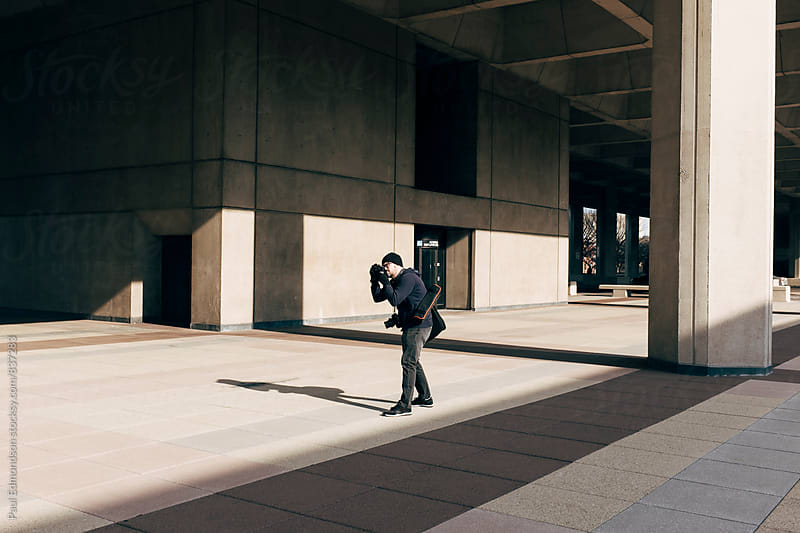 Man taking photographs near modern buildings by Paul Edmondson for Stocksy United
