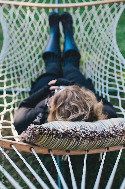 woman rests in a hammock by Margaret Vincent for Stocksy United