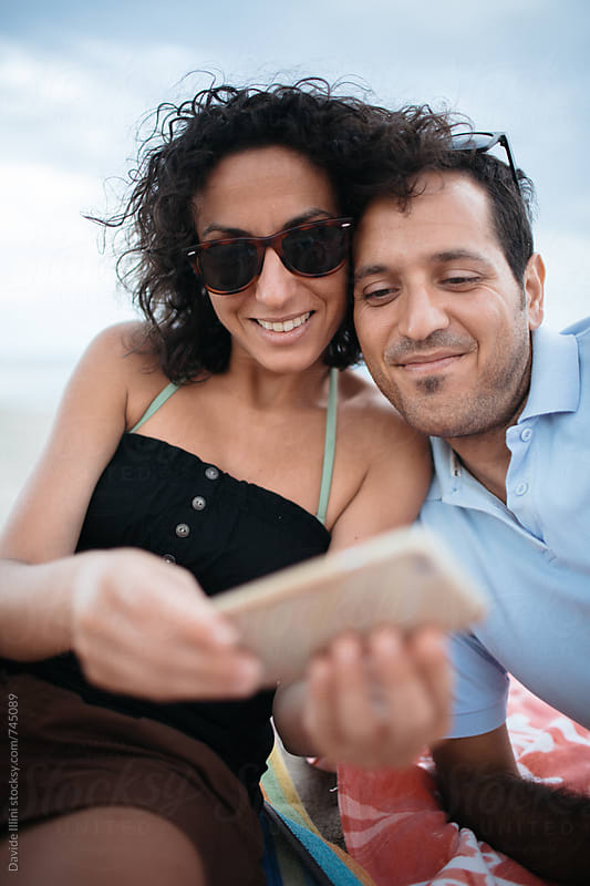 Happy couple using mobile phone on the beach by Davide Illini for Stocksy United