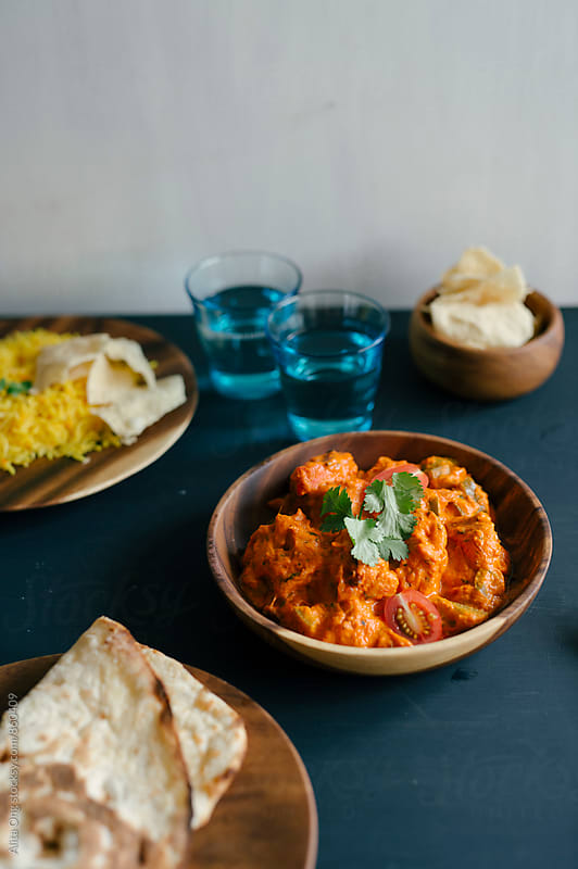 Chicken tikka masala served with naan bread by Alita Ong for Stocksy United