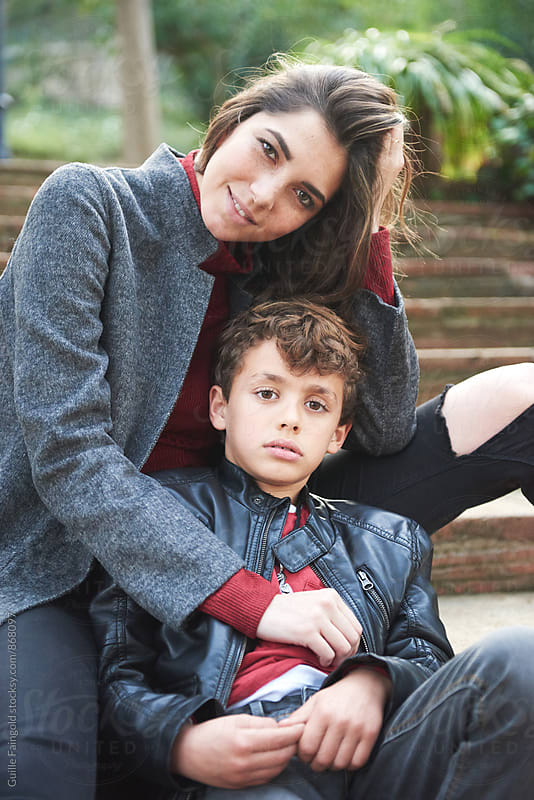 Sad boy and smiling young mother looking at camera while sitting on steps by Guille Faingold for Stocksy United