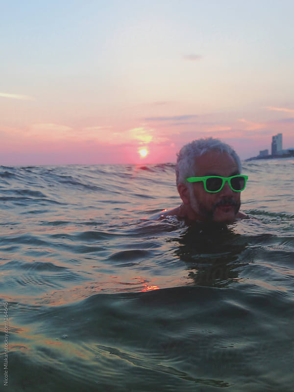 Man swimming in the ocean at sunset with sunglasses on by Nicole Mlakar for Stocksy United
