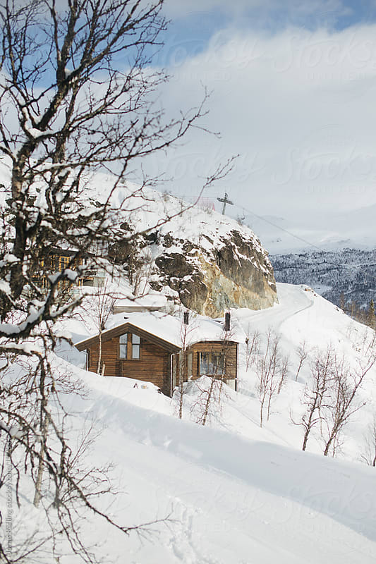 Hut covered and surronded by snow in the mountains by Jonas Räfling for Stocksy United