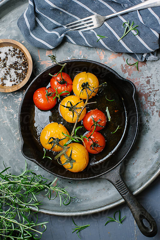 Confit tomatoes in a cast iron skillet, on a metal background. by Darren Muir for Stocksy United